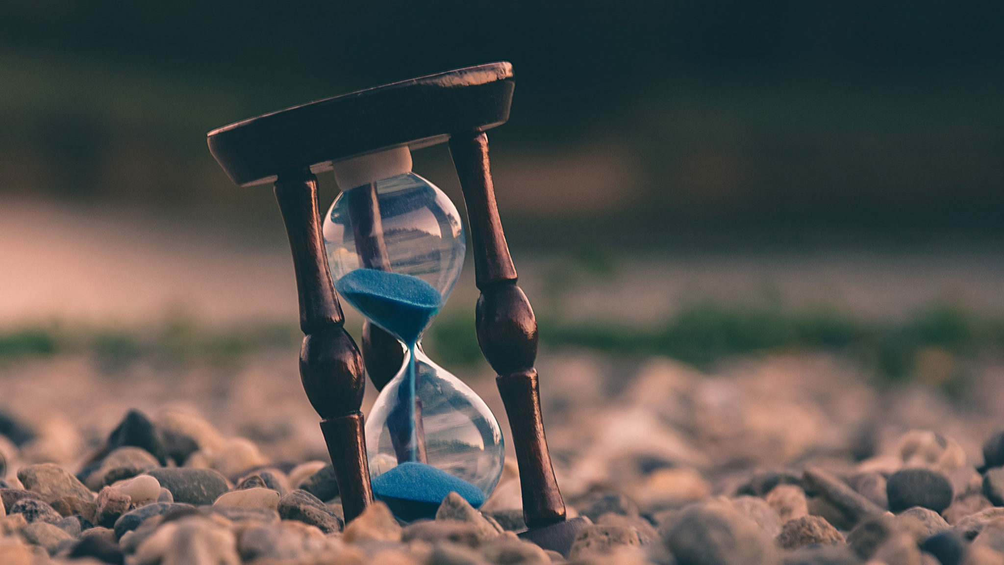 Hourglass with blue sand on a rocky surface.